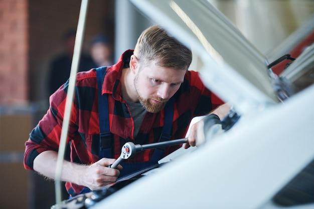 Professioneller meister der autoreparatur mit einem der handwerkzeuge beim bücken über den offenen motor in der werkstatt