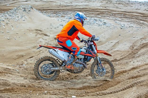Professioneller motocross-motorradfahrer fährt über die straße.