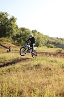 Professioneller motorradfahrer im helm, der beim motorradfahren auf unebener strecke einen schritt nach oben macht