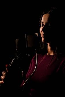 Professioneller musiker, der ein neues lied im studio aufnimmt.