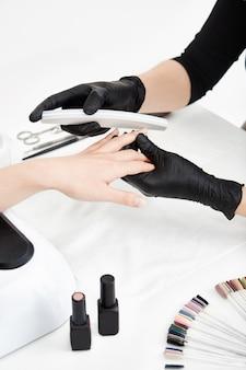 Professioneller nageltechniker, der nägel feilt, bevor er nagellack aufträgt.