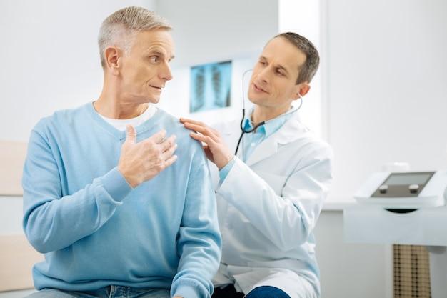 Professioneller osteopath. schlauer hübscher männlicher arzt, der hinter seinem patienten sitzt und stethoskop trägt, während er ihn untersucht