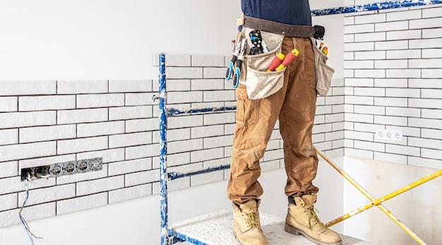 Professioneller overall mit werkzeugen auf der reparaturstelle.