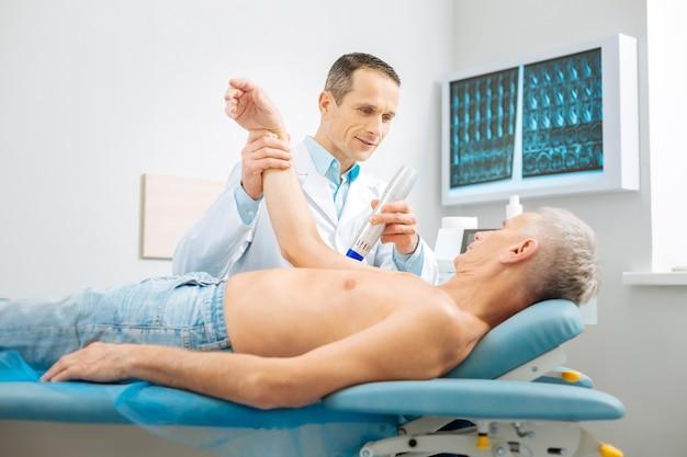Professioneller physiotherapeut. erfreut, netter, gutaussehender arzt, der steht, hört seinen patienten und überprüft seine gesundheit, während er seine arbeit erledigt
