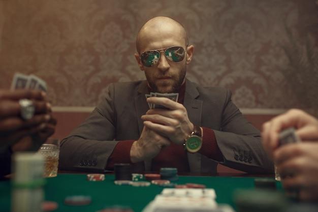 Professioneller pokerspieler mit sonnenbrille, der im casino spielt. sucht