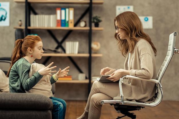 Professioneller psychologe. schöne, gut aussehende frau, die dem mädchen zuhört, während sie eine psychologische sitzung mit ihr hat Premium Fotos