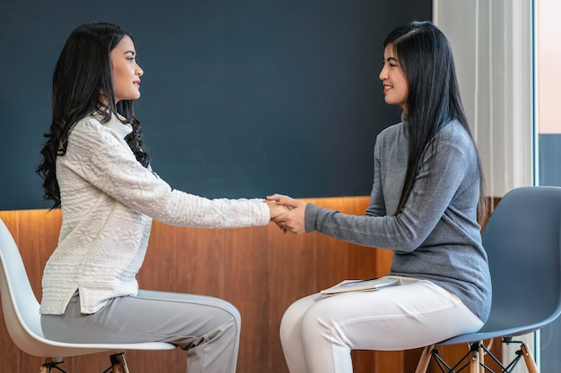 Professioneller psychologendoktor der asiatin, der den weiblichen patienten im wohnzimmer das konsultieren gibt