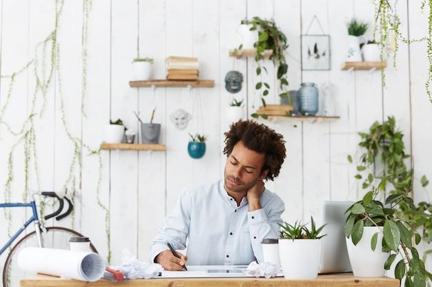 Professioneller qualifizierter erfolgreicher ingenieur einer großen baufirma, die an zeichnungen arbeitet