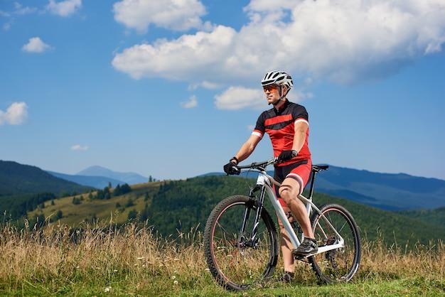 Professioneller radfahrer in sportbekleidung und helm radfahren mountainbike