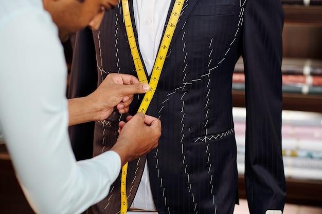 Professioneller schneider, der in seinem modernen studio maßgeschneiderte anzüge für kunden herstellt