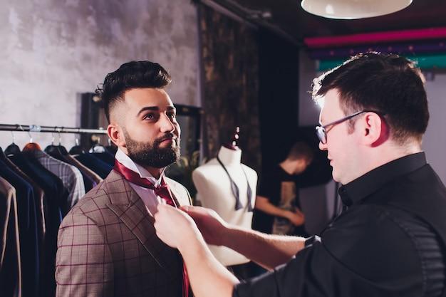 Professioneller schneider, der messungen für nähanzug in der schneiderei vornimmt