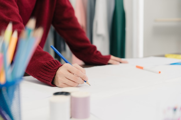 Professioneller schöner asiatischer weiblicher modedesigner, der mit gewebeskizzen arbeitet