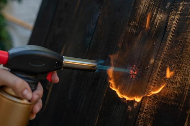 Professioneller schreiner mit alter traditioneller japanischer technik. brennen von holzbrettern mit gasbrenner. diy-prozess.