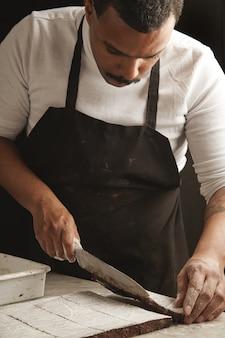Professioneller schwarzer bäcker schneidet scheiben von großem schokoladenkuchen mit zuckerpulver zum verpacken und verkaufen