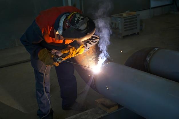Professioneller schweißer arbeitet mit manuellem lichtbogenschweißen.