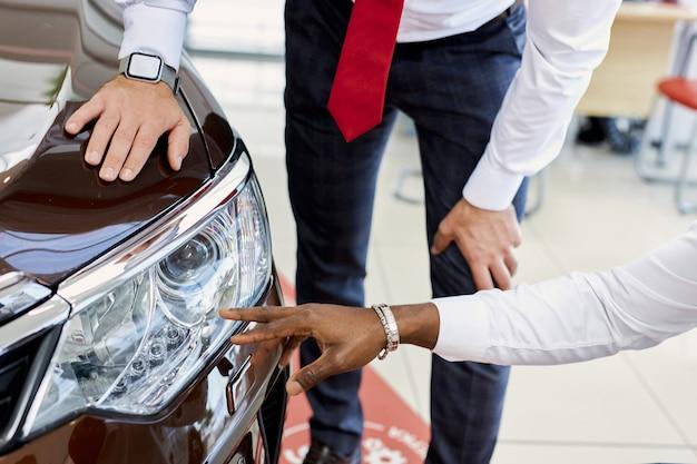 Professioneller, selbstbewusster verkäufer spricht über die scheinwerfer des autos
