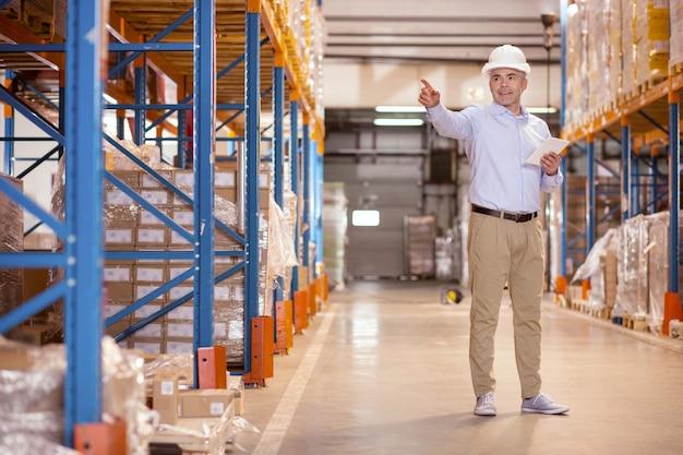 Professioneller sicherheitsmanager, der mit seiner hand zeigt, während er im lager arbeitet