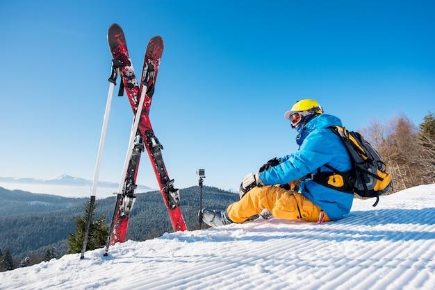Professioneller skifahrer, der auf einem berg sitzt