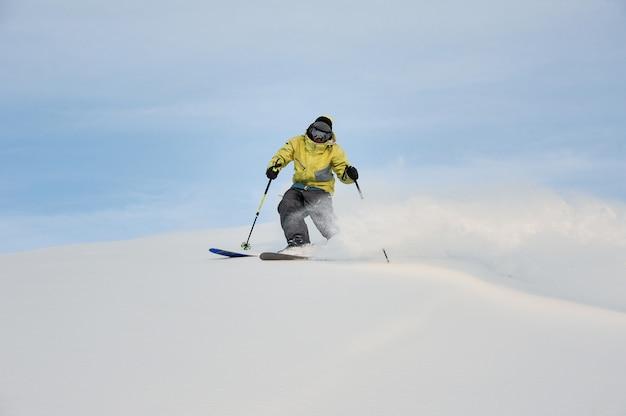 Professioneller snowboarder, der den berghang hinunter rutscht