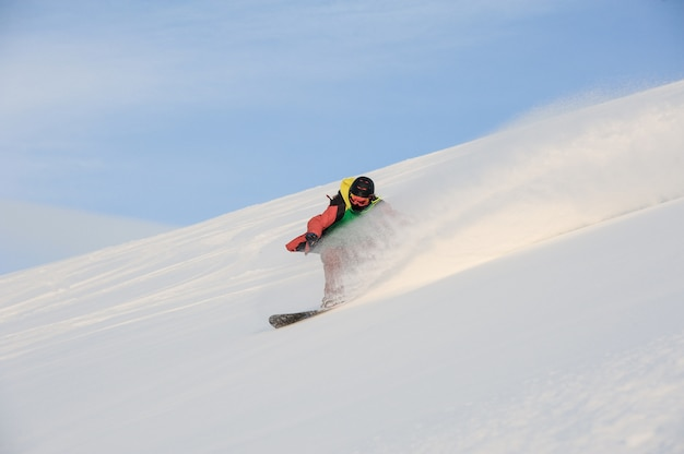 Professioneller snowboarder, der den schneebedeckten hang hinunter fährt