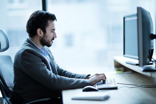 Professioneller softwareentwickler, der im büro am schreibtisch arbeitet
