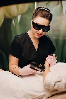 Professioneller spa-mitarbeiter, der eine hand-haarentfernungssitzung mit einer frau hat, während er eine brille trägt und eine maschine benutzt