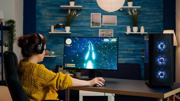 Professioneller spieler, der ein ego-shooter-online-videospiel auf einem leistungsstarken pc mit bunten neon-led-lichtern spielt. cyber-performance auf dem pc in einem stilvollen raum während des gaming-turniers