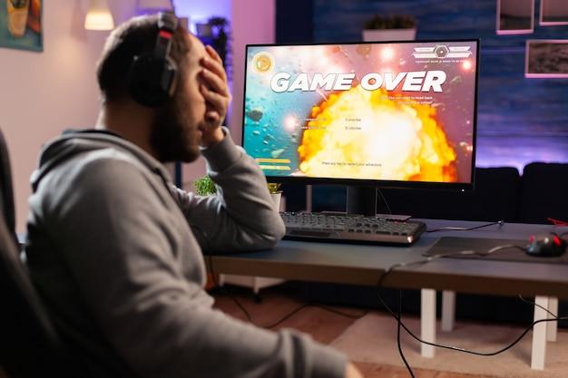 Professioneller spieler, der ein weltraum-shooter-videospiel auf dem computer für die meisterschaft spielt. cyber-performance auf einem leistungsstarken pc im spielzimmer zu hause während eines online-turniers