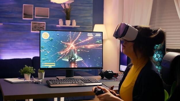 Professioneller spieler mit vr-brille, der auf einem gaming-stuhl sitzt und ein online-weltraum-shooter-spiel spielt