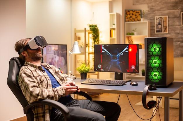 Professioneller spieler mit vr-headset, um spät in der nacht in seinem wohnzimmer auf einem leistungsstarken pc zu spielen