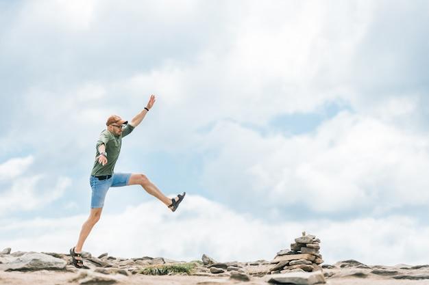 Professioneller sporstman, der im freien an der natur vorwärts springt. trittsteine für reisende.