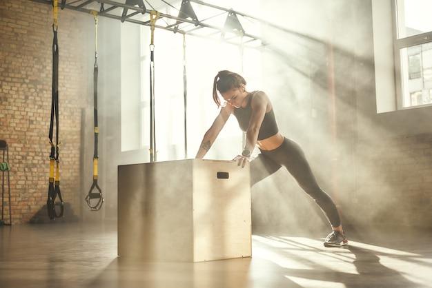 Professioneller sport junge schöne athletische frau in sportkleidung macht liegestütze im fitnessstudio