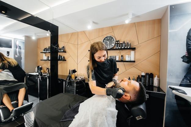 Professioneller stylist in einem modernen, stilvollen friseurladen rasiert und schneidet einem jungen mann die haare