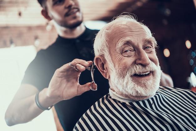 Professioneller stylist schert alten mann im barbershop