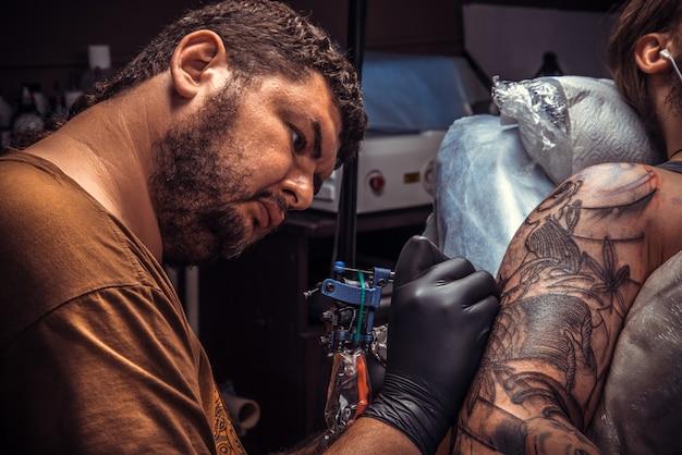 Professioneller tätowierer, der im tattoo-studio tätowiert.