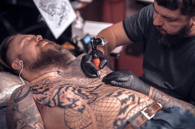 Professioneller tätowierer konzentrierte sich auf seine arbeit in seinem salon.