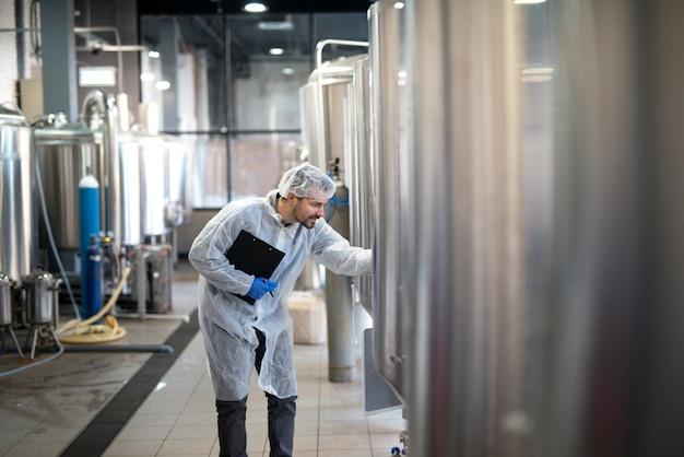 Professioneller technologe, der den industriellen prozess in der produktionsanlage kontrolliert