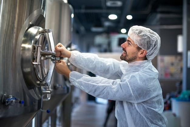 Professioneller technologe, der industrietank in produktionsanlage öffnet