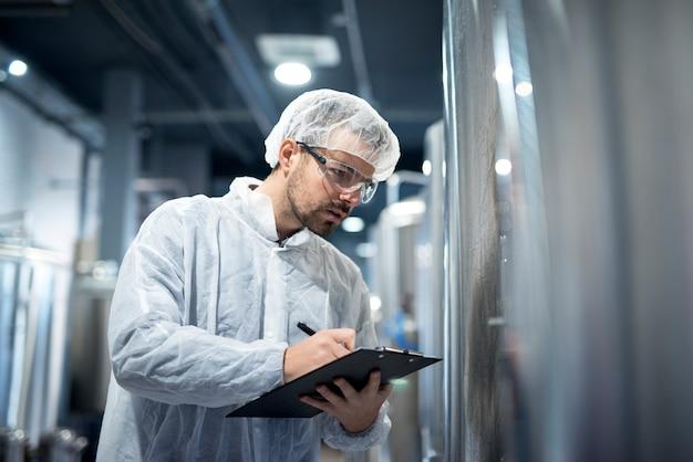 Professioneller technologe in weißer schutzuniform, der den industriellen prozess in der produktionsanlage kontrolliert