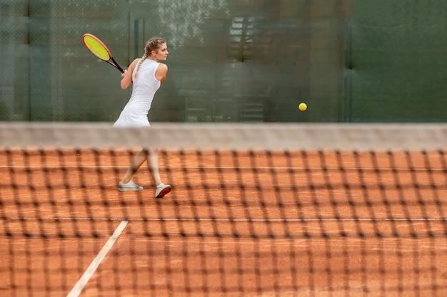 Professioneller tennisspieler, der an einem sonnigen tag tennis auf einem sandtennisplatz spielt.