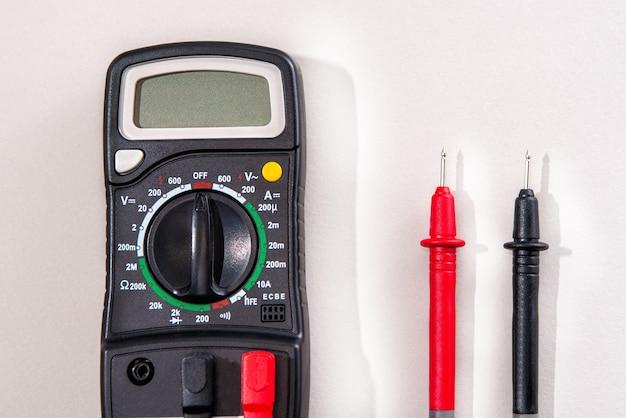 Professioneller tester auf hellgrauem hintergrund. professionelles elektrikerwerkzeug.
