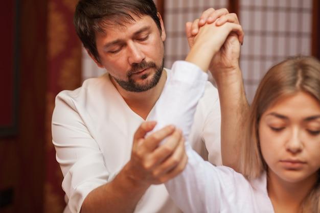 Professioneller thailändischer massagetherapeut, der mit seiner kundin arbeitet und ihren arm in seiner badekurortmitte ausdehnt. geernteter schuss einer frau, die thailändische massage am badekurort erhält. hotels, resorts, reisen