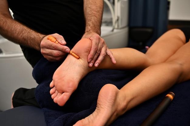 Professioneller therapeut, der im spa eine traditionelle thailändische fußreflexzonenmassage mit stock gibt. thai-fußmassage im spa-salon