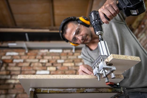 Professioneller tischler, der im haus mit holz und bauwerkzeugen arbeitet.