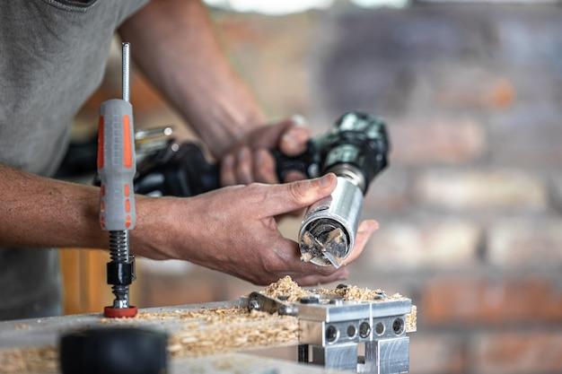 Professioneller tischler, der mit einem scharnierbohrer arbeitet, mit holz arbeitet