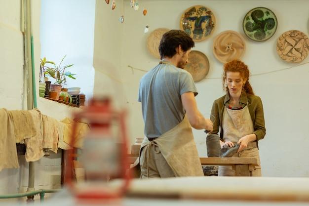 Professioneller töpfermeister. konzentrierte keramikfacharbeiter, die sich in der nähe des arbeitstisches aufhalten und sich auf ihre aufgaben konzentrieren