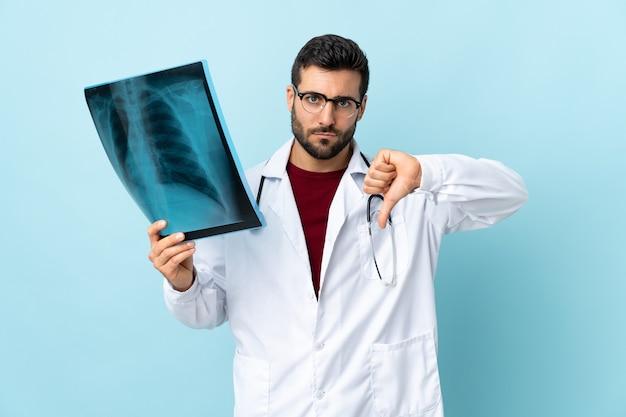 Professioneller traumatologe, der radiographie lokalisiert auf blau hält, das daumen unten zeichen zeigt