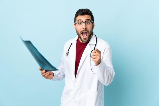 Professioneller traumatologe, der radiographie lokalisiert auf blauer wand hält, zeigt finger auf sie