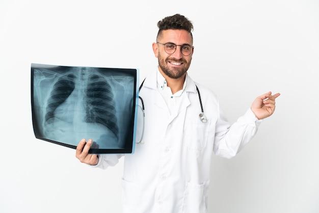 Professioneller traumatologe isoliert auf weißem hintergrund, der mit dem finger zur seite zeigt