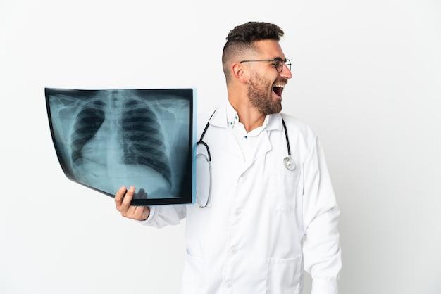 Professioneller traumatologe isoliert auf weißem hintergrund lachend in seitenlage